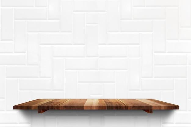 Prateleira de prancha de madeira vazia no fundo da parede de azulejos brancos
