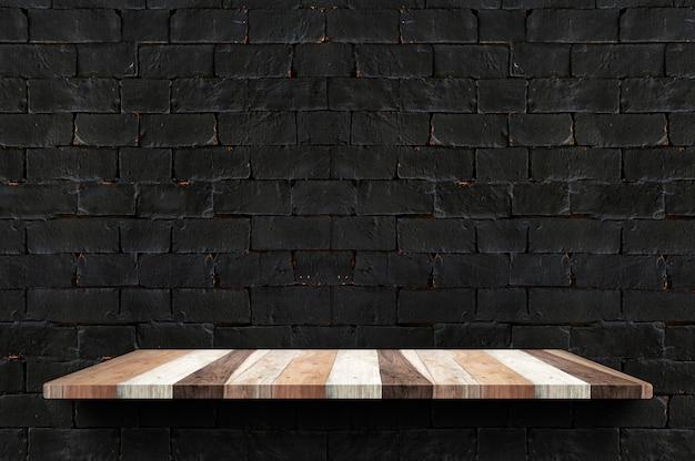 Prateleira de tábua de madeira vazia na parede de tijolo preto