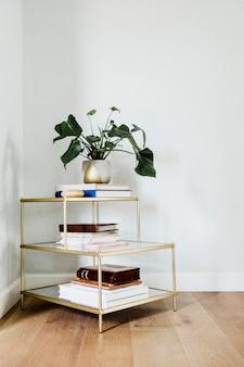 Prateleira dourada com livros e um pote de folhas