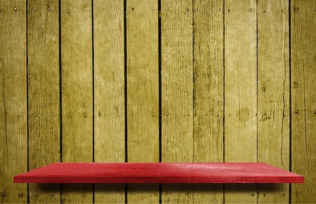 Prateleira vermelha no fundo de madeira amarelo da textura da parede.
