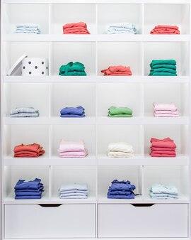 Prateleiras brancas com roupas, vitrines