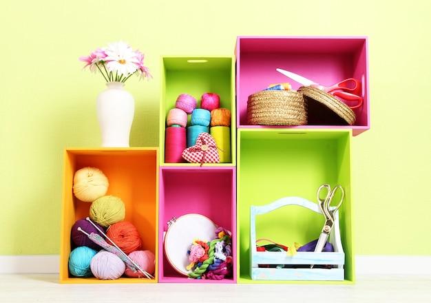 Prateleiras coloridas de cores diferentes com utensílios no fundo da parede