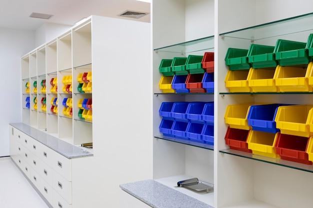Prateleiras de farmácia modernas com caixas multicoloridas para armazenamento.