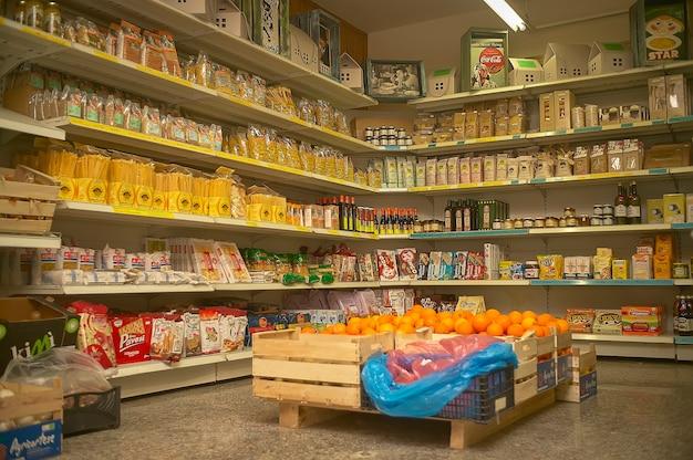Prateleiras de loja de conveniência cheias de embalagens de alimentos e caixas de frutas.