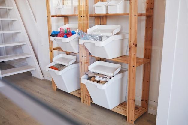 Prateleiras de madeira com recipientes de plástico para coleta seletiva em casa