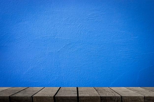 Prateleiras de madeira vazias com parede de cimento azul para exposição do produto