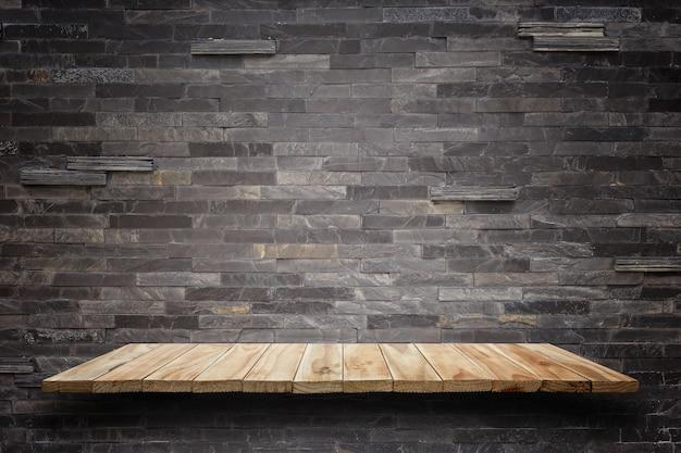Prateleiras de madeira vazias e fundo da parede de pedra. para a exposição do produto