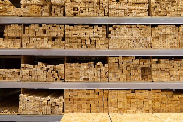 Prateleiras de uma loja de ferragens forradas com pilhas de tábuas de madeira.