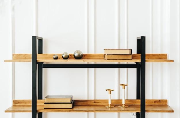 Prateleiras decorativas de madeira na sala de estar com livros e castiçais