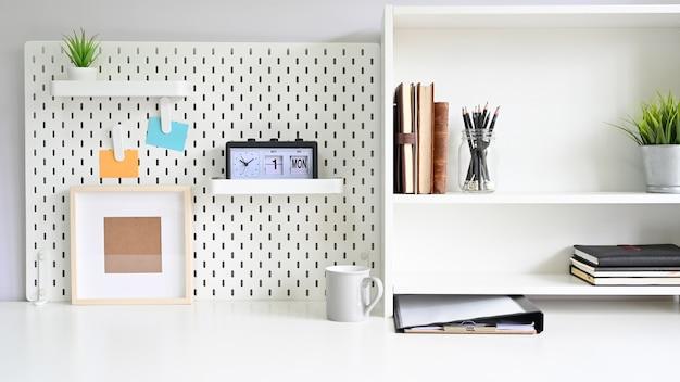 Prateleiras e pegboard com material de escritório na mesa do espaço de trabalho