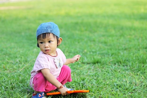 Prática asiática da menina da criança do bebê a andar no campo de grama.