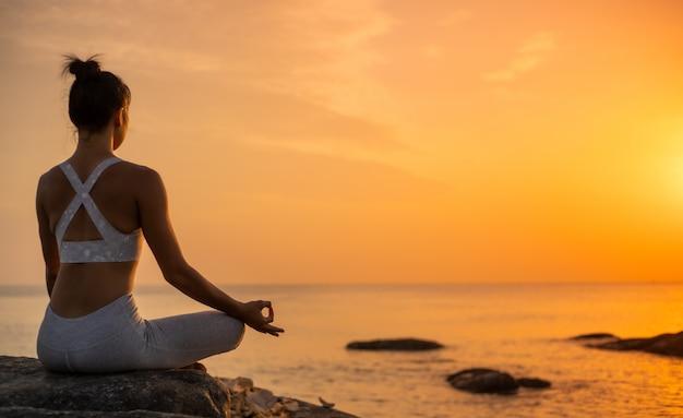 Prática de garota asiática yoga na praia dia de manhã do nascer do sol