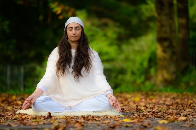 Prática de ioga no parque de outono por uma garota