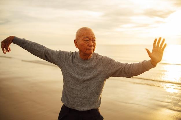 Prática de velho asiático senior tai chi e yoga pose na praia nascer do sol