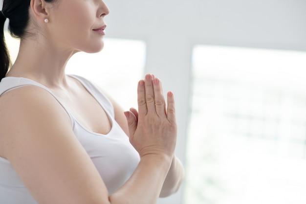 Prática de yoga. close-up de mãos femininas realizando namastê, pressionando as mãos juntas