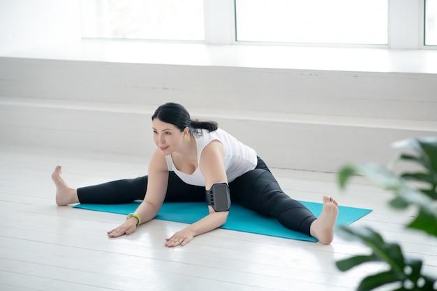 Prática de yoga. morena mulher sentada no tapete, fazendo o racha