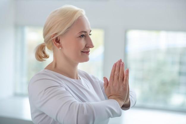 Prática de yoga. mulher loira madura realizando namastê, pressionando as mãos juntas