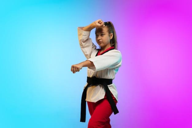 Prática. karatê, garota de taekwondo com faixa preta isolada em fundo gradiente em luz de néon. pequeno modelo caucasiano, garoto do esporte, treinamento em movimento e ação. esporte, movimento, conceito de infância.