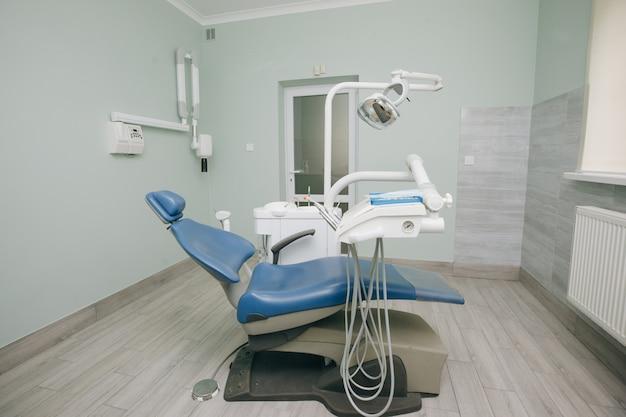 Prática odontológica moderna. cadeira odontológica e outros acessórios utilizados pelos dentistas em azul