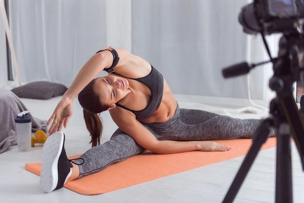 Praticando esporte. mulher jovem de cabelos escuros, atlética e muito alegre, fazendo exercícios enquanto está sentada no tapete e gravando um vídeo para seu blog