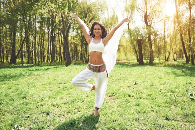 Praticando ioga de uma linda garota pela manhã em ervas sob as palavras do sol.