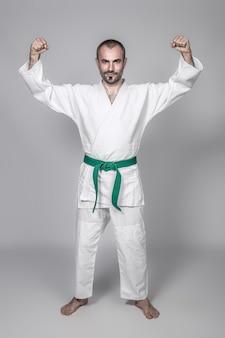 Praticante de artes marciais com os braços erguidos em vitória.