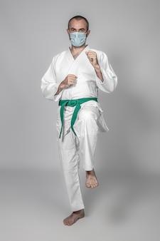 Praticante de artes marciais usando uma máscara para se proteger da infecção por covid-19. conceito de saúde no esporte