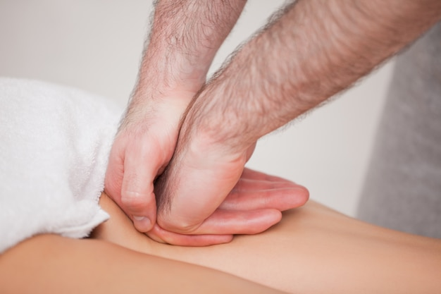 Praticante massageando a coxa de seu paciente em um quarto
