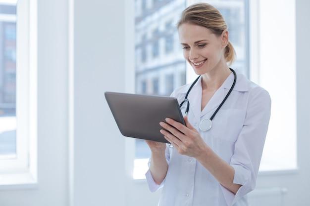 Praticante profissional concentrado e animado, desfrutando do horário de trabalho no hospital, enquanto expressa interesse e usa o tablet