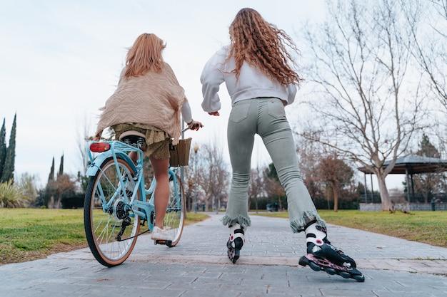 Praticar esportes em família enquanto comemoramos o dia das mães. o filho de patins, a irmã de patins e a mãe de bicicleta.