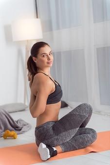 Praticar exercícios em casa. mulher jovem de cabelos escuros, atlética e feliz, sorrindo e praticando esportes enquanto está sentada no tapete