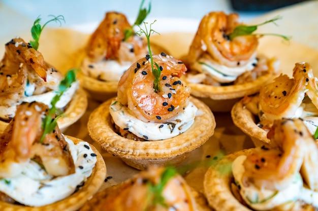 Prático bufê de canapés com camarão alimenta pequenos sanduíches no festival