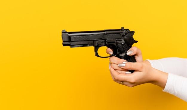 Pratique o uso de uma arma de autodefesa para a mão de uma mulher asiática e as armas sendo treinadas para atirar