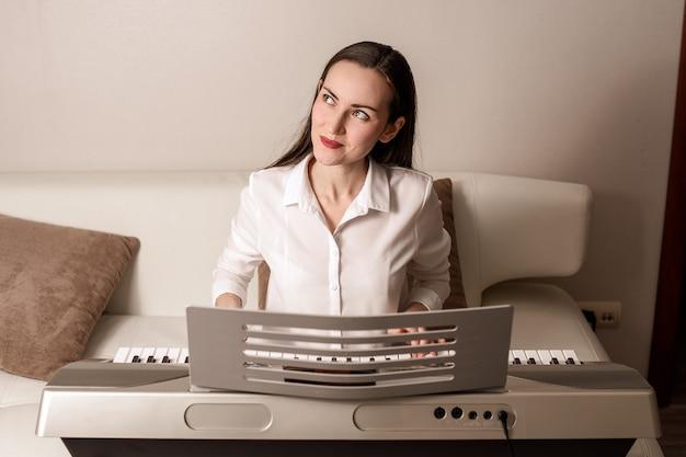Pratique tocando o sintetizador, retrato frontal de uma mulher em um piano eletrônico