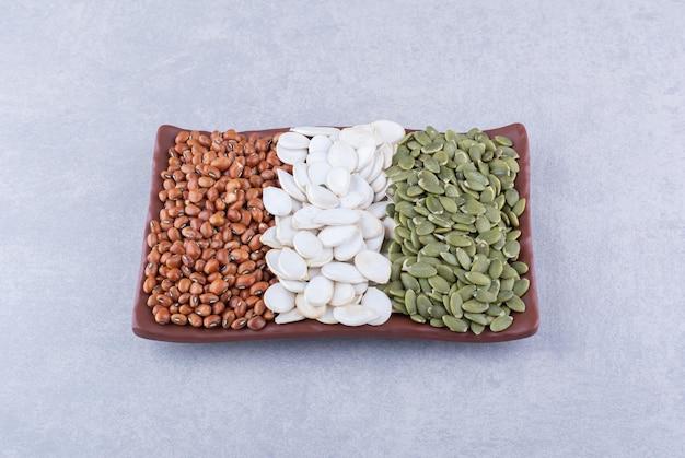 Prato abastecido com feijão vermelho, sementes de abóbora brancas e pepitas na superfície de mármore