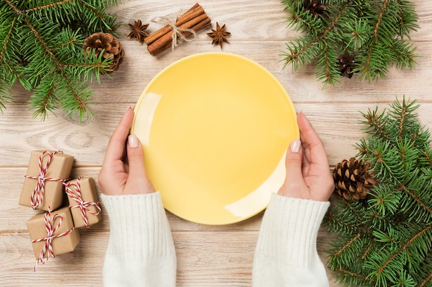 Prato amarelo vazio na superfície de madeira com decoração de natal