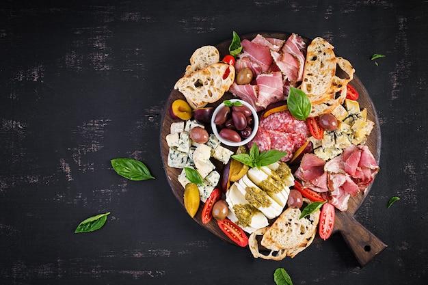 Prato antipasto com presunto, presunto, salame, queijo azul, mussarela com pesto e azeitonas. vista superior, sobrecarga
