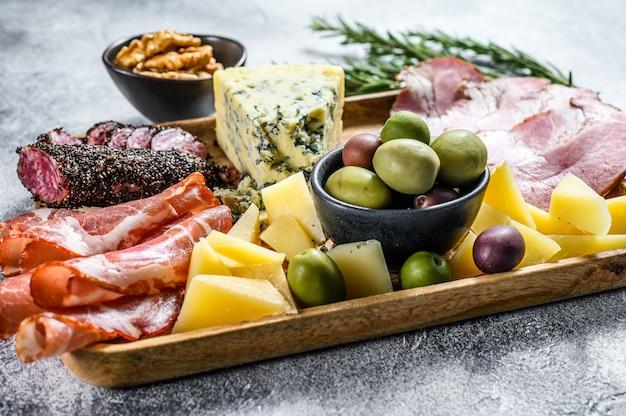 Prato antipasto com presunto, presunto, salame, queijo azul, mussarela e azeitonas. vista do topo