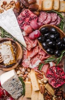 Prato antipasto italiano tradicional. queijos variados na tábua de madeira. queijo brie, fatias de cheddar, gogonzola, uvas nozes, azeitonas, presunto, alecrim e copo de vinho tinto. vista do topo
