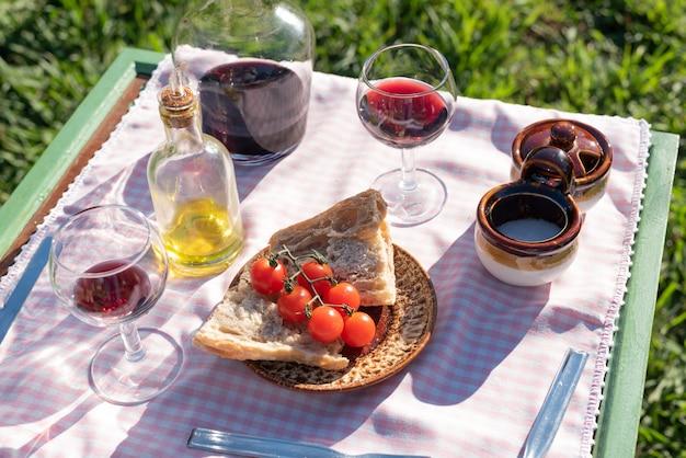 Prato aperitivo espanhol com vinho para piquenique no jardim ao pôr do sol