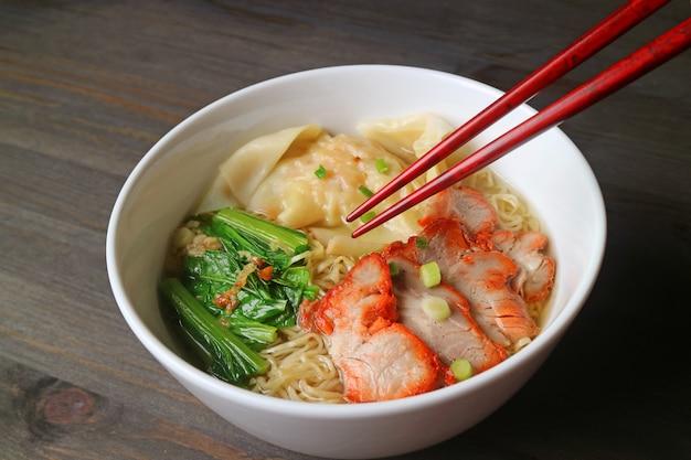 Prato asiático de bolinho de massa de wonton de porco assado e sopa de macarrão de ovo com legumes
