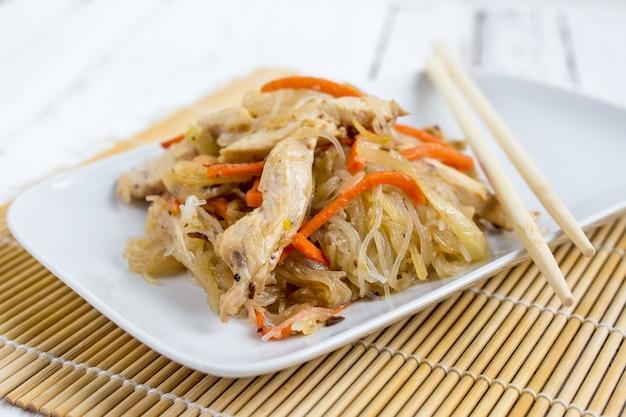 Prato asiático de chapchae de macarrão de vidro com frango e legumes