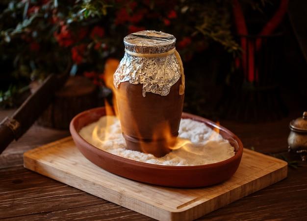 Prato azerbaijano cozido em jarra de cerâmica coberta com papel alumínio em chamas