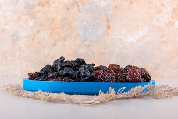 Prato azul cheio de saborosas ameixas secas em fundo branco. foto de alta qualidade