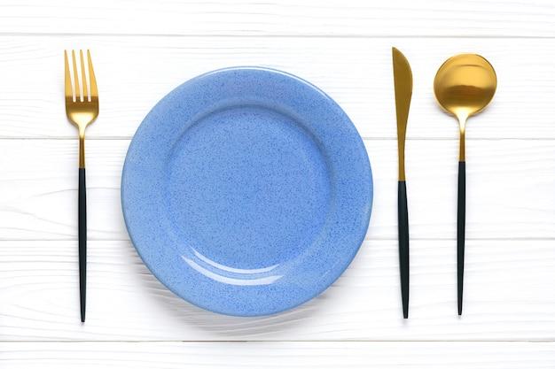 Prato azul com talheres de ouro