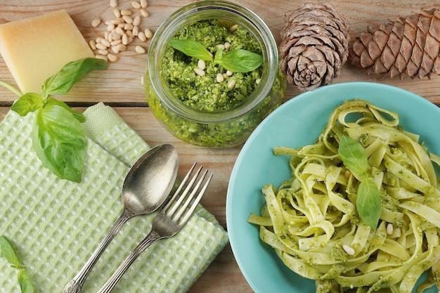 Prato azul com tolyatelli com molho pesto de uma jarra de vidro, cones de cedro, queijo e manjericão, guardanapo verde e talheres em uma mesa de tábua de madeira