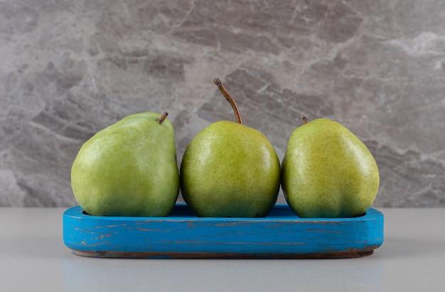 Prato azul com um punhado de peras no mármore
