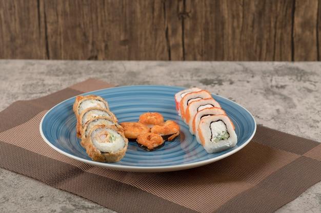 Prato azul com vários rolos de sushi na mesa de mármore