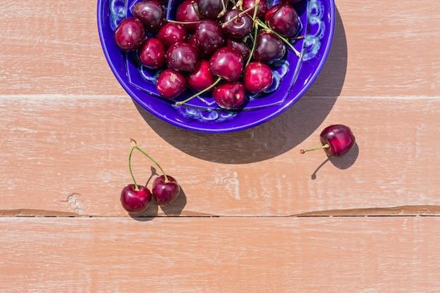 Prato azul de doce de cereja madura na mesa de madeira