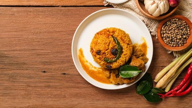 Prato biryani de carneiro indiano servido na mesa de madeira. comida típica da índia, feita com carne de cabra misturada com especiarias e arroz basmati Foto Premium